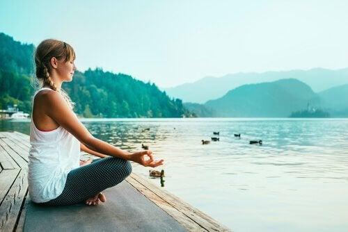 Eine junge Frau meditiert an einem See.