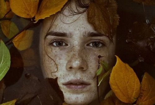 Frau, die mit bunten Blättern bedeckt ist