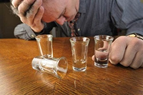 Betrunkener Mann hinter Schnapsgläsern