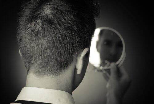 Mann, der in einen Spiegel blickt