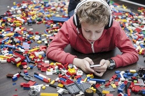 Kind, das inmitten von Spielzeug am Handy ist