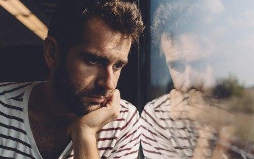 Mann, der traurig aus einem Fenster schaut