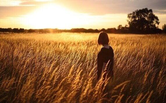 Frau steht in einem Weizenfeld