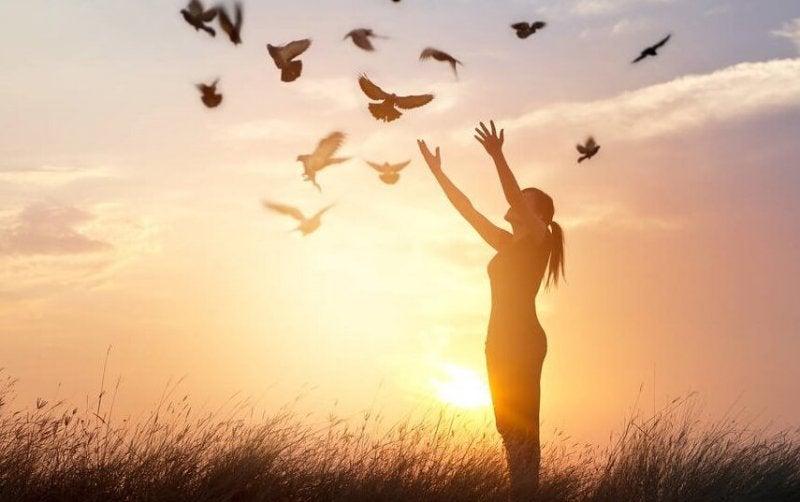 Frau streckt ihre Hände zu fliegenden Tauben aus
