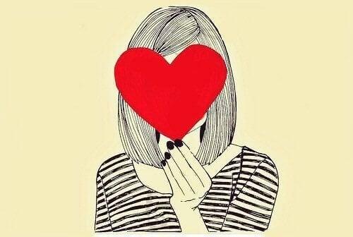 Frau mit einem Herzen vor dem Gesicht