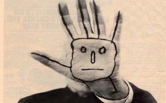 Ausgestreckte Hand mit aufgemaltem Gesicht