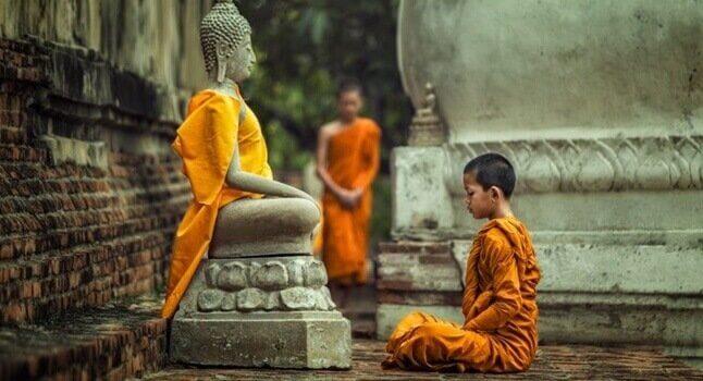 Junger Mönch sitzt vor einer Buddhastatue