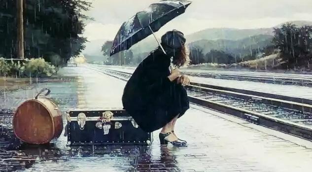 Frau mit Regenschirm wartet am Bahngleis
