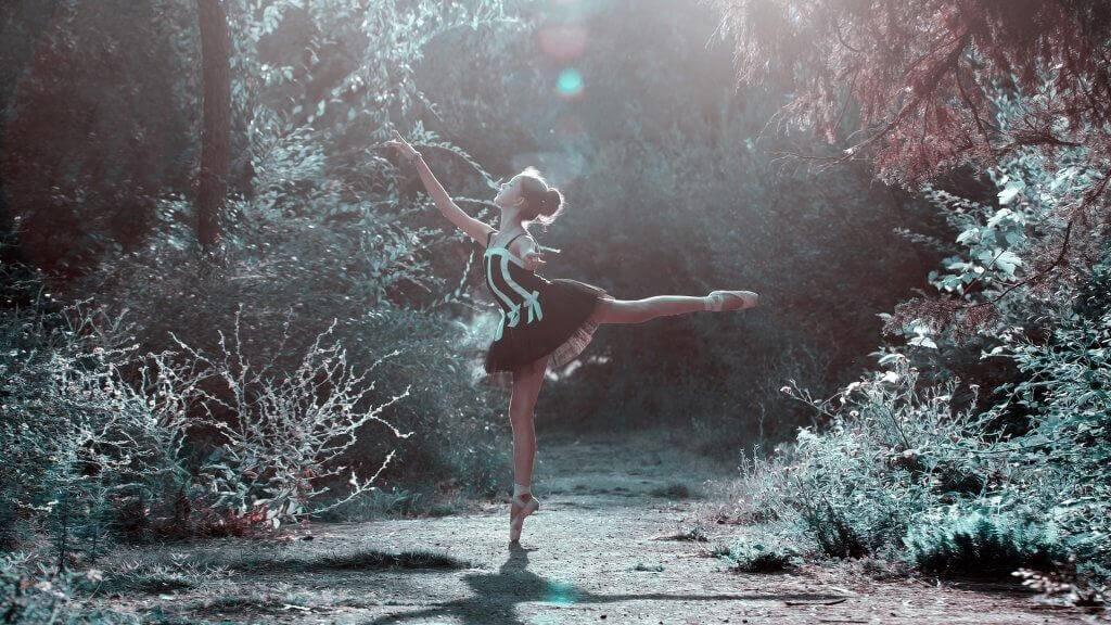Mädchen auf Spitzenschuhen tanzt im schwarz-weißen Ballettkleid auf einer Waldlichtung.