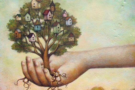 Hand hält einen Baum mit Häuschen in der Baumkrone