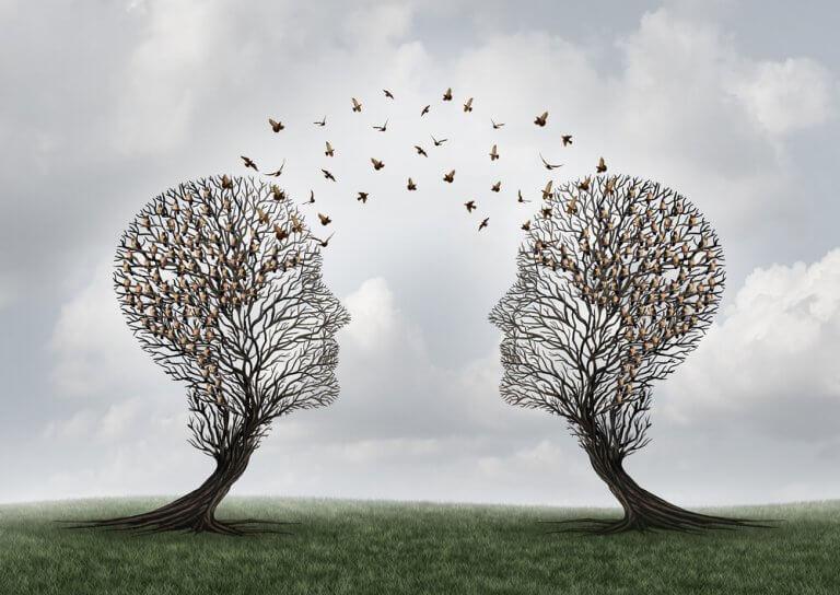 Zwei Bäume in Form von Köpfen, aus denen Vögel emporfliegen
