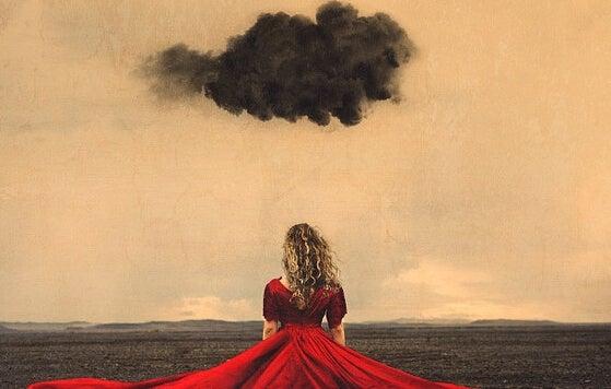 Dunkle Gewitterwolke schwebt über einem Mädchen im roten Kleid