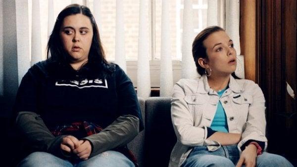 Zwei Freunde sitzen auf dem Couch.