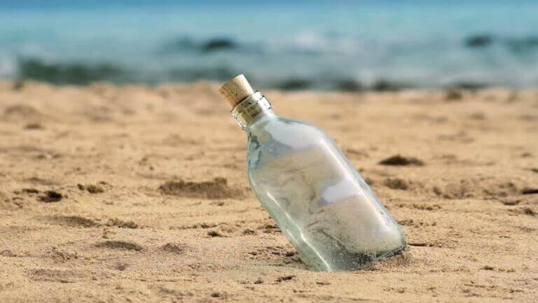 Glasflasche steckt im Sand