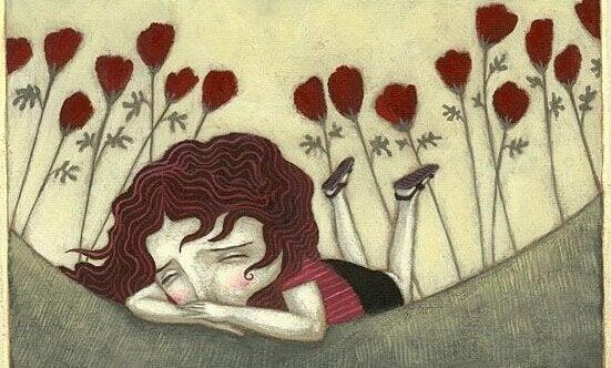 Ein trauriges Maedchen weint im Blumenfeld