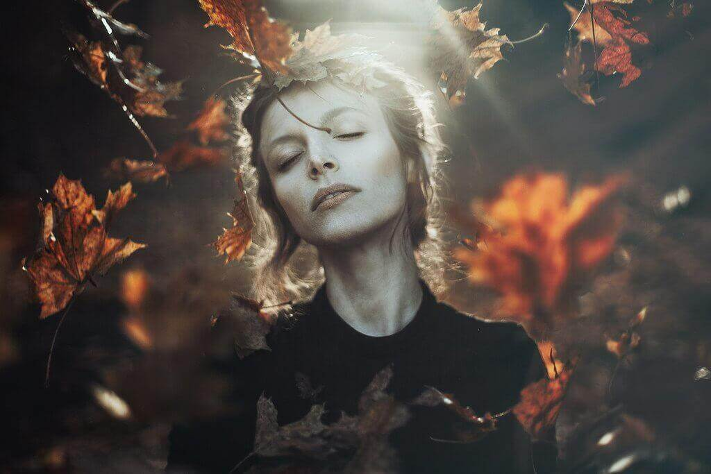 Frau im Herbst umgeben von Blättern