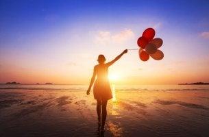 Entdecke deine Fähigkeiten - junge Frau mit Ballons am Strand
