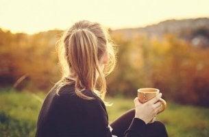 Mit sich selbst zufrieden sein - Frau mit Kaffeetasse im Grünen