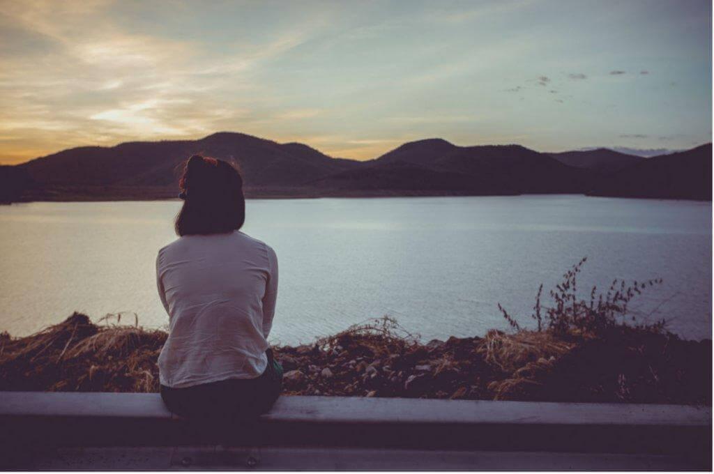 Frau schaut auf einen See