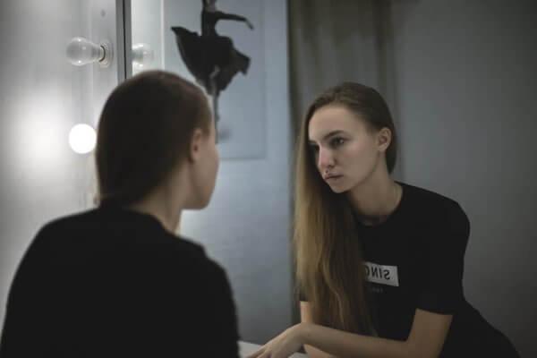 Mädchen schaut sich im Spiegel an