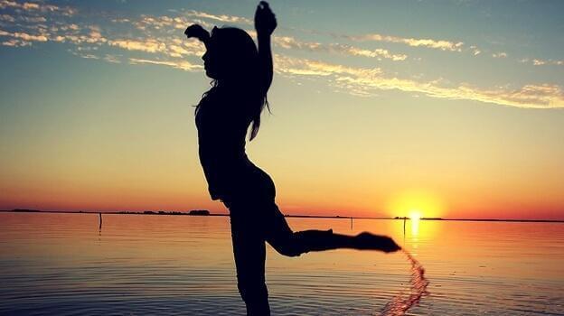 Frau im Schattenumriss tanzt im Sand vor Sonnenuntergang am Wasser.