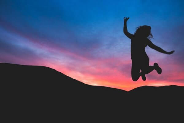 Frau springt vor Sonnenuntergang in die Luft