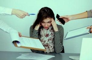 Mobbing am Arbeitsplatz - gestresste Frau am Schreibtisch