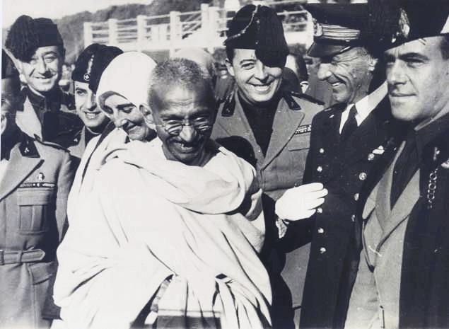 Gandhi umgeben von Menschen in Uniform