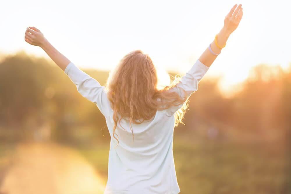 Lebensfrohe Frau streckt Hände in den Himmel