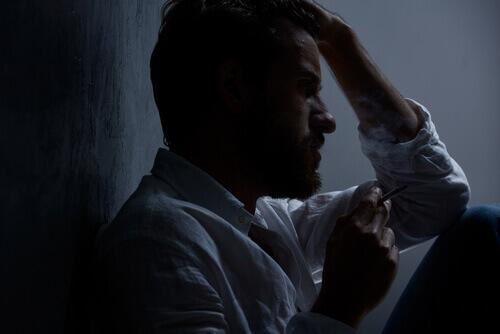 Verängstigter Mann sitzt im Dunkeln
