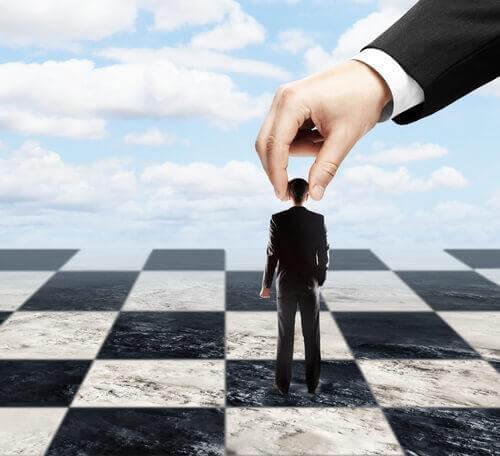 Mann wird auf einem Schachbrett von jemand anderem geführt