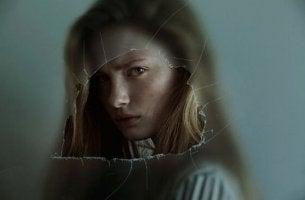 Passiv-aggressive Persönlichkeitsstörung - Frau hinter einer eingeschlagenen Scheibe