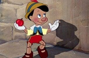 Bedeutung von Bildung - Pinocchio mit einem Apfel in der Hand