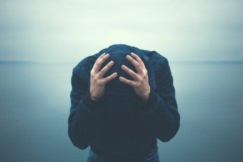 Mann hält seinen Kopf mit beiden Händen