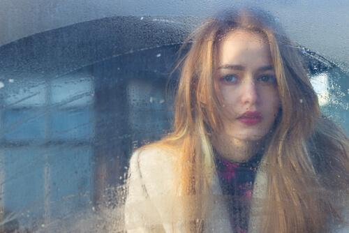 Frau schaut durch Fenster, an dem Wasser kondensiert