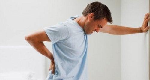 Erschöpfter Mann mit Rückenschmerzen