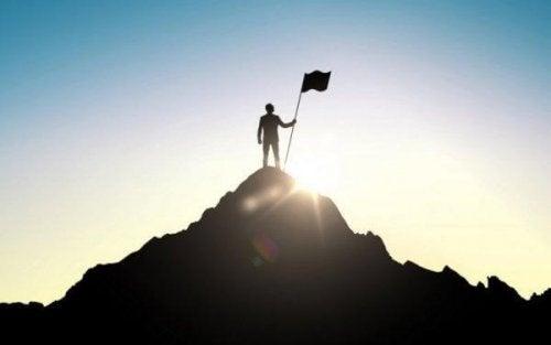 Mann, der auf einer Bergspitze steht