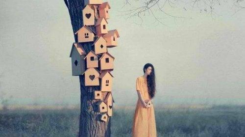 Nachdenkliche Frau, die neben einem Baum voller Vogelhäuser steht