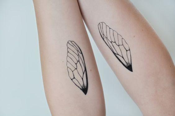 Zwei Arme mit je einem Flügeltattoo als Zeichen von emotionaler Unabhängigkeit