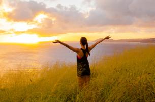Träumen Flügel verleihen - Eine Frau schaut auf die aufgehende Sonne, breitet die Arme aus.