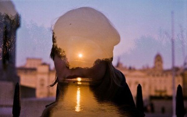 Das Licht der untergehenden Sonne spiegelt sich auf Wasserflächen und im Gesicht einer Frau.