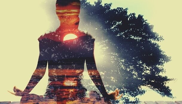 Frau meditiert vor Sonnenuntergang