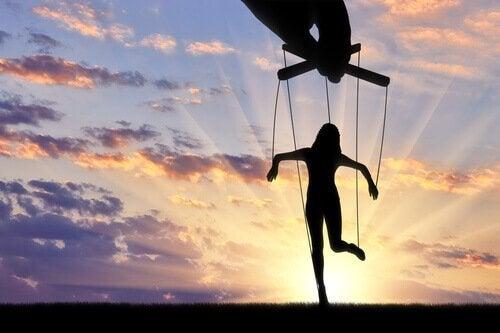 Eine Hand führt eine Marionette vor einem Sonnenaufgang.
