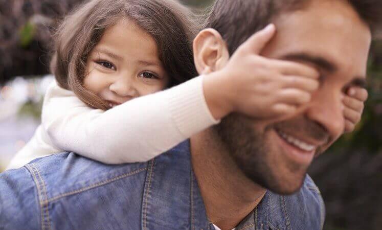Lachendes Mädchen verdeckt ihrem Vater die Augen