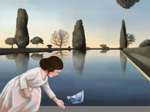 Frau setzt Papierschiff auf Teich