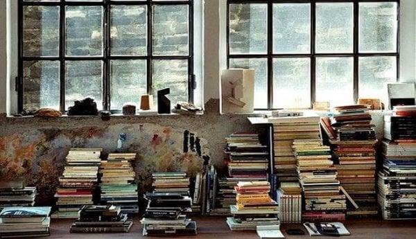 Aufgestapelte Bücher vor einem Fenster