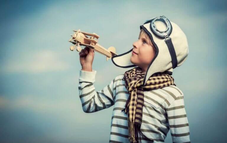 Ein Junge spielt mit einem Flugzeug aus Holz.