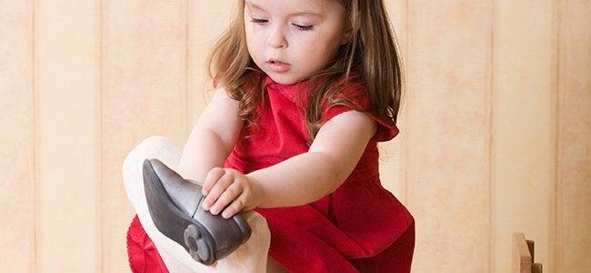 Ein kleines Mädchen zieht seinen rechten Schuh an.