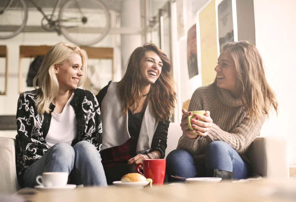 Eine Gruppe von Freundinnen sitzt zusammen und trinkt Kaffee. Alle sind positiv gestimmt.