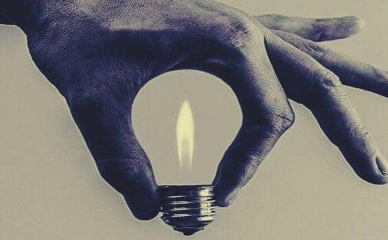Eine Hand formt eine Glühbirne mit Flamme